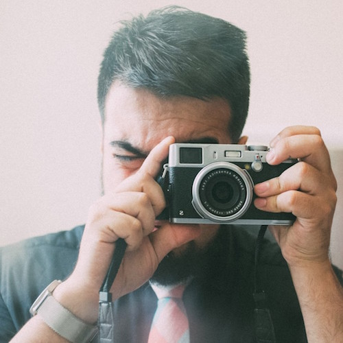 A lovely photograph of Ali Karbassi holding a camera.